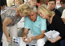 ADDS THE NAME OF THE WOMAN, LEFT - Carl Hiaasen, center, brother of Rob Hiaasen, one of the journalists killed in the shooting at The Capital Gazette newspaper offices, is consoled by his sisters Barb, left, and Judy during a memorial service, Monday, July 2, 2018, in Owings Mills, Md. (AP Photo/Patrick Semansky)
