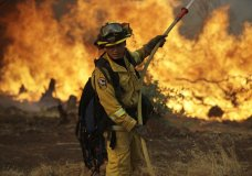 A firefighter makes a stand in front of an advancing wildfire as it approaches a residence Saturday, July 28, 2018, in Redding ,Calif. (AP Photo/Marcio Jose Sanchez)