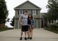 In this May 24, 2018 photo, Jennifer Tadeo-Uscanga, 17, and her stepdad, Steve Stegall, stand outside the Kansas City, Mo., home they shared with wife and mother Letty Stegall. Stegall, who lived in the United States for 20 years, was deported back to Mexico in March, leaving the pair to fill the void left by her absence. (AP Photo/Charlie Riedel)