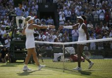 Kiki Bertens of the Netherlands, left, meets Venus Williams of the US at the net after defeating her in their women's singles match on the fifth day at the Wimbledon Tennis Championships in London, Friday July 6, 2018. (AP Photo/Tim Ireland)
