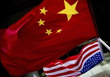FILE - In this Nov. 7, 2012, filephoto, U.S. and Chinese national flags are hung outside a hotel during the U.S. Presidential election event, organized by the U.S. embassy in Beijing. A government report is outlining how spy services from China, Russia and Iran are hard at work trying to steal trade secrets and proprietary information from U.S. companies, government labs and universities.(AP Photo/Andy Wong, File)