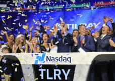 FILE- In this July 19, 2018, file photo Brendan Kennedy, third from right in front, CEO and founder of British Columbia-based Tilray Inc., a major Canadian marijuana grower, leads cheers as confetti falls to celebrate his company's IPO (TLRY) at Nasdaq in New York. Investors are craving marijuana stocks as Canada prepares to legalize pot next month, leading to giant gains for Canada-based companies listed on U.S. exchanges. (AP Photo/Bebeto Matthews, File)