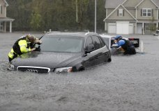 Members of the North Carolina Task Force urban search and rescue team check cars in a flooded neighborhood looking for residents who stayed behind as Florence continues to dump heavy rain in Fayetteville, N.C., Sunday, Sept. 16, 2018. (AP Photo/David Goldman)