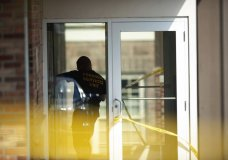 An officer investigates a shooting that occurred in the Masontown borough municipal center on Wednesday, September 19, 2018, in Masontown, Pa. A gunman opened fire outside a crowded courtroom Wednesday afternoon, shooting at police and others before an officer fired multiple shots at him, killing him. (Andrew Stein/Post-Gazette via AP)