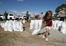 Chloe Heeden, 4, from Virginia Beach, Va., drags a sandbag to her father's car, Wednesday, Sept. 12, 2018, in Virginia Beach, Va., as Hurricane Florence moves towards the eastern shore. The National Hurricane Center's projected track had Florence hovering off the southern North Carolina coast from Thursday night until landfall Saturday morning or so, about a day later than previously expected. The track also shifted somewhat south and west, throwing Georgia into peril as Florence moves inland. (AP Photo/Alex Brandon)