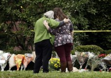 Two people support each other in front of flowers at a makeshift memorial at the Tree of Life Synagogue in Pittsburgh, Sunday, Oct. 28, 2018. Robert Bowers, the suspect in Saturday's mass shooting at the synagogue, expressed hatred of Jews during the rampage and told officers afterward that Jews were committing genocide and he wanted them all to die, according to charging documents made public Sunday. (AP Photo/Matt Rourke)