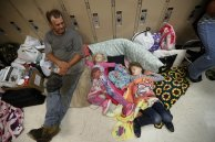 CORRECTS HURRICANE NAME TO MICHAEL NOT MATTHEW - Earnest Sweet sits while his daughters Terri, 4, center, and Anna, 7, sleep at an evacuation shelter set up at Rutherford High School, in advance of Hurricane Michael, which is expected to make landfall today, in Panama City Beach, Fla., Wednesday, Oct. 10, 2018. (AP Photo/Gerald Herbert)