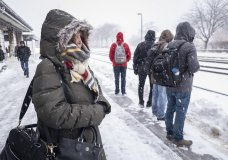 Carol Vervoort waits at the Naperville Metra station in Chicago. A wintry storm brought blizzard-like conditions to parts of the Midwest early Monday, Nov. 26, 2018, grounding hundreds of flights and causing slick roads for commuters as they returned to work after the Thanksgiving weekend.(Rich Hein/Chicago Sun-Times via AP)