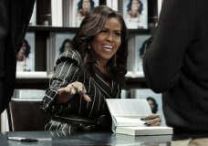 """FILE - In this Nov. 30, 2018, file photo, Former First Lady Michelle Obama signs books during an appearance for her book, """"Becoming,"""" in New York. Sales for Obama's memoir have topped 3 million and the former first lady is extending her book tour into 2019. Live Nation and Crown Publishing announced Tuesday, Dec. 11, that Obama will have 21 events next year, six of them in Europe. (AP Photo/Richard Drew, File)"""