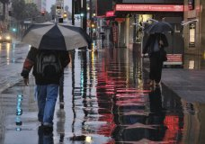 Pedestrians make their way along a rain soaked Hollywood Blvd. in Los Angeles on Thursday, Jan. 17, 2019. The latest in a series of Pacific Ocean storms pounded California with rain and snow Thursday, prompting officials to put communities on alert for mudslides and flooding and making travel treacherous. (AP Photo/Richard Vogel)