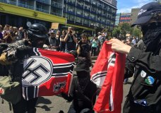 FILE - In this Aug. 4, 2018, file photo, counter protesters tear a Nazi flag, in Portland, Ore. A member of Portland's city council says she is shocked by a newspaper report that the commander for the police rapid response team exchanged friendly text messages with a leader of far-right protests that have rocked the city. Councilwoman Jo Ann Hardesty said the reporting in Willamette Week on Thursday, Feb. 14, 2019, confirms there are members of the Portland police force who work in collusion with right-wing extremists. (AP Photo/Manuel Valdes, File)