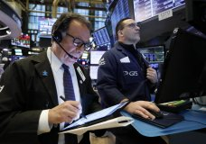 Trader Sal Suarino, left, and specialist Anthony Matesic work on the floor of the New York Stock Exchange, Tuesday, March 5, 2019. Stocks are opening slightly lower on Wall Street led by losses in banks and technology companies. (AP Photo/Richard Drew)