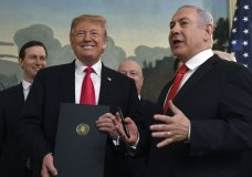 President Donald Trump smiles as he holds a proclamation as Israeli Prime Minister Benjamin Netanyahu, right, speaks in the Diplomatic Reception Room at the White House in Washington, Monday, March 25, 2019. Trump signed an official proclamation formally recognizing Israel's sovereignty over the Golan Heights. (AP Photo/Susan Walsh)