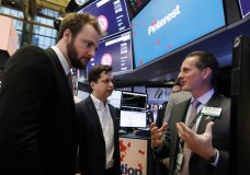 Pinterest co-founder & CEO Ben Silbermann, center, and fellow co-founder and chief product officer Evan Sharp, left, meet with specialist Glenn Carell on the New York Stock Exchange trading floor, Thursday, April 18, 2019, before the company's IPO. (AP Photo/Richard Drew)