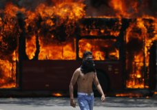 An anti-government protester walks near a bus that was set on fire by opponents of Venezuela's President Nicolas Maduro during clashes between rebel and loyalist soldiers in Caracas, Venezuela, Tuesday, April 30, 2019. Venezuelan opposition leader Juan Guaidó took to the streets with a small contingent of heavily armed troops early Tuesday in a bold and risky call for the military to rise up and oust Maduro. (AP Photo/Fernando Llano)