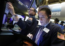 FILE- In this April 2, 2019, file photo specialist Gregg Maloney, left, and trader Tommy Kalikas work on the floor of the New York Stock Exchange. The U.S. stock market opens at 9:30 a.m. EDT on Tuesday, April 9. (AP Photo/Richard Drew, File)