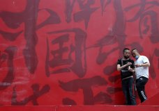 """Workers share cigarettes near a booth promoting Made in China with Chinese calligraphy for """"China Trendy"""" in Beijing on Wednesday, May 8, 2019. China's exports fell in April amid a punishing tariff war with Washington, adding to pressure on Beijing on the eve of negotiations aimed at settling the fight over its technology ambitions. (AP Photo/Ng Han Guan)"""