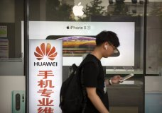 """A man looks at his smartphone as he walks past an electronics shop advertising phones from Huawei and Apple in Beijing, Friday, May 24, 2019. Stepping up a propaganda offensive against Washington, China's state media on Friday accused the U.S. of seeking to """"colonize global business"""" by targeting telecom equipment giant Huawei and other Chinese companies. (AP Photo/Mark Schiefelbein)"""