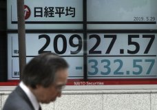 A man walks past an electronic stock board showing Japan's Nikkei 225 index at a securities firm in Tokyo Wednesday, May 29, 2019. Asian shares slipped Wednesday on expectations that a trade dispute between China and the United States would simmer and possibly weigh on growth.(AP Photo/Eugene Hoshiko)