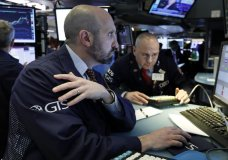 FILE- In this March 12, 2019, file photo specialists James Denaro, left, and Mario Picone work at a post on the floor of the New York Stock Exchange. The U.S. stock market opens at 9:30 a.m. EDT on Friday, May 3. (AP Photo/Richard Drew, File)