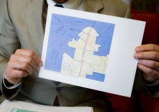 FILE - In this Thursday, April 11, 2019, file photo David Niven, a professor of political science at the University of Cincinnati, holds a map demonstrating a gerrymandered Ohio district in Cincinnati. The Supreme Court said, by a 5-4 vote on Thursday, June 27, 2019, that claims of partisan gerrymandering do not belong in federal court. The court's conservative, Republican-appointed majority says that voters and elected officials should be the arbiters of what is a political dispute The decision effectively reverses the outcome of rulings in Maryland, Michigan, North Carolina and Ohio, where courts had ordered new maps drawn. (AP Photo/John Minchillo, File)