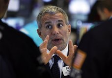 FILE - In this June 11, 2019, file photo specialist Anthony Rinaldi talks with colleagues on the floor of the New York Stock Exchange. The U.S. stock market opens at 9:30 a.m. EDT on Friday, June 21. (AP Photo/Richard Drew, File)