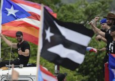 Ricky Martin, holding a Puerto Rican flag and a rainbow banner, flashes a thumbs up as he joins in with thousands of Puerto Ricans for what many are expecting to be one of the biggest protests ever seen in the U.S. territory, with irate islanders pledging to drive Gov. Ricardo Rossello from office, in San Juan, Puerto Rico, Monday, July 22, 2019. Protesters are demanding Rossello step down for his involvement in a private chat in which he used profanities to describe an ex-New York City councilwoman and a federal control board overseeing the island's finance. (AP Photo/Carlos Giusti)