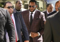 FILE - In this June 26, 2019, file photo, R&B singer R. Kelly, center, arrives at the Leighton Criminal Court building for an arraignment on sex-related felonies in Chicago. R. Kelly, already facing sexual abuse charges brought by Illinois prosecutors, was arrested in Chicago Thursday, July 11, 2019 on a federal grand jury indictment listing 13 counts including sex crimes and obstruction of justice. (AP Photo/Amr Alfiky, File)