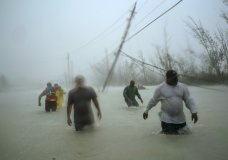 Volunteers walk under the wind and rain from Hurricane Dorian through a flooded road as they work to rescue families near the Causarina bridge in Freeport, Grand Bahama, Bahamas, Tuesday, Sept. 3, 2019. The storm's punishing winds and muddy brown floodwaters devastated thousands of homes, crippled hospitals and trapped people in attics. (AP Photo/Ramon Espinosa)