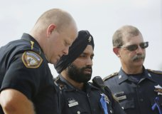 In this Aug. 30, 2015, photo, Harris County Sheriff's Deputy Sandeep Dhaliwal, center, grieves with Deputies Dixon, left, and Seibert, right, at a memorial for Deputy Darren Goforth, at the Chevron where he was killed, in Houston. Dhaliwal was shot and killed while making a traffic stop Friday, Sept. 27, 2019, near Houston. (Jon Shapley/Houston Chronicle via AP)
