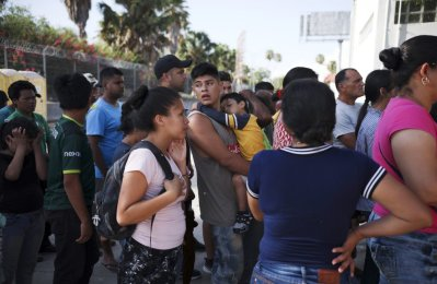 FILE - In this Aug. 1, 2019 file photo, migrants line up in Matamoros, Mexico, for a meal donated by volunteers from the U.S., at the foot of the Puerta Mexico bridge that crosses to Brownsville, Texas. A federal appeals court has put on hold a ruling that blocked a Trump administration policy that would prevent migrants from seeking asylum along the entire southwest border. The 9th U.S. Circuit Court of Appeals issued a stay Tuesday, Sept. 10, 2019 that put the ruling by U.S. District Judge Jon Tigar on hold for now. That means the administration's asylum policy is blocked in the border states of California and Arizona but not in New Mexico and Texas. (AP Photo/Emilio Espejel. Fi