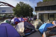 FILE - In this Aug. 30, 2019 file photo, asylum seekers walk by an encampment near the Gateway International Bridge in Matamoros, Mexico. A federal appeals court has put on hold a ruling that blocked a Trump administration policy that would prevent migrants from seeking asylum along the entire southwest border. The 9th U.S. Circuit Court of Appeals issued a stay Tuesday, Sept. 10, 2019 that put the ruling by U.S. District Judge Jon Tigar on hold for now. That means the administration's asylum policy is blocked in the border states of California and Arizona but not in New Mexico and Texas. (AP Photo/Veronica G. Cardenas, File)