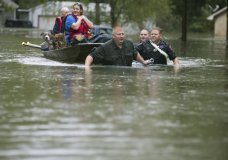Splendora Police Lt. Troy Teller, left, Cpl. Jacob Rutherford and Mike Jones pull a boat carrying Anita McFadden and Fred Stewart from their flooded neighborhood inundated by rain from Tropical Depression Imelda on Thursday, Sept. 19, 2019, in Spendora, Texas. (Brett Coomer/Houston Chronicle via AP)