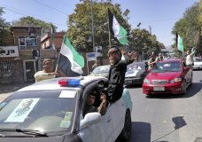 """Afghans travel in convoy with cars decorated with black flags and portraits of late Commander Ahmad Shah Massoud marking the 18th anniversary of his death, in Kabul, Afghanistan, Monday, Sept. 9, 2019. Afghans are bracing for a possible new wave of Taliban violence after President Donald Trump abruptly called off talks with the insurgent group, which vows to continue its fight against what it calls """"foreign occupation."""" (AP Photo/Ebrahim Noroozi)"""