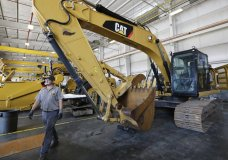 In this Sept. 18, 2019, photo a Puckett Machinery Company technician walks past a new heavy duty Caterpillar excavator that awaits modification at Puckett Machinery Company in Flowood, Miss. On Tuesday, Oct. 1, the Institute for Supply Management, a trade group of purchasing managers, issues its index of manufacturing activity for September. (AP Photo/Rogelio V. Solis)
