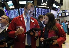 Traders William Lawrence, center, and Ashley Lara confer as they work on the floor of the New York Stock Exchange, Monday, Oct. 21, 2019. Stocks are opening higher on Wall Street Monday as investors get set for a busy week of earnings reports. (AP Photo/Richard Drew)