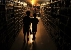 Elijah Carter 11, left, and Robert Haralson, 12, help shop for their parents in a darkened Olivers Supermarket in the Rincon Valley community, Wednesday, Oct. 23, 2019, in Santa Rosa, Calif. The west side of the store was lit by patio lights powered by a generator as power was shut off again by Pacific Gas & Electric Co. due to high fire danger. (Kent Porter/The Press Democrat via AP)