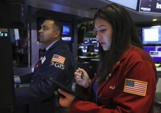 Specialist Dilip Patel, left, and trader Ashley Lara work on the floor of the New York Stock Exchange, Friday, Nov. 15, 2019. Stocks are opening broadly higher on Wall Street as hopes continued to grow that the U.S. and China were moving closer to a deal on trade. (AP Photo/Richard Drew)