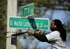 FILE - In this April, 20, 2019, file photo, public works employee Jerry Brooks changes a street sign from The Paseo to Dr. Martin Luther King Jr. Blvd. in Kansas City, Mo. More than 50 years after King was assassinated, the city's efforts to honor the civil rights leader has met opposition from citizens opposed to the renaming of The Paseo, one of the city's iconic boulevards. (AP Photo/Charlie Riedel, File)