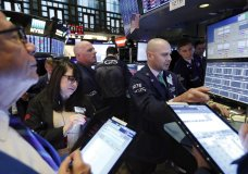 Specialist Mario Picone, right, works with traders at his post on the floor of the New York Stock Exchange, Wednesday, Nov. 20, 2019. Stocks are opening slightly lower on Wall Street led by declines in technology and communications companies. (AP Photo/Richard Drew)