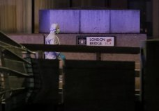 "A police forensic officer walks by a sign where a man was shot dead by police on London Bridge following an incident in London, Friday, Nov. 29, 2019. British police shot a man on London Bridge in the heart of Britain's capital on Friday after a stabbing that left several people wounded. The Metropolitan Police force said the circumstances were still unclear, but ""as a precaution, we are currently responding to this incident as though it is terror-related."" (AP Photo/Matt Dunham)"