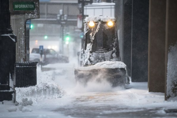 A sidewalk cleaner brushes snow off the sidewalk on Superior Street in Duluth, Minn., Wednesday, Nov. 27, 2019. (Alex Kormann/Star Tribune via AP)
