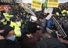 """Residents scuffle with police officers during a rally to protest the government's decision to quarantine South Koreans returning from Wuhan in their home town in Jincheon, South Korea, Thursday, Jan. 30, 2020. The death toll rose to 170 in the new virus outbreak in China on Thursday as foreign evacuees from the worst-hit region begin returning home under close observation and world health officials expressed """"great concern"""" that the disease is starting to spread between people outside of China. (Lim Hun-jung/Yonhap via AP)"""