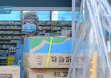 A clerk wearing a face mask and a plastic bag stands in a pharmacy in Wuhan in central China's Hubei Province, Friday, Jan. 31, 2020. The U.S. advised against all travel to China as the number of cases of a worrying new virus spiked more than tenfold in a week, including the highest death toll in a 24-hour period reported Friday. (AP Photo/Arek Rataj)
