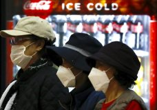 Tourists from Korea wearing protective masks walk with their belongings while waiting for a flight back to South Korea at the Ben Gurion airport near Tel Aviv, Israel, Monday, Feb. 24, 2020. (AP Photo/Ariel Schalit)