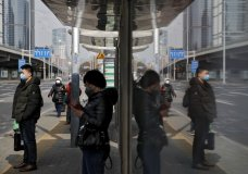 Commuters wearing protective face masks wait for buses at a stop in the Central Business District in Beijing, Monday, March 2, 2020. China's manufacturing plunged in February as anti-virus controls shut down much of the world's second-largest economy, but companies are confident activity will revive following government stimulus efforts, according to two surveys. (AP Photo/Andy Wong)