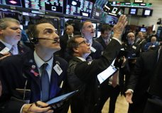 Traders gather at a post on the floor of the New York Stock Exchange, Wednesday, March 4, 2020. Stocks are surging in early trading on Wall Street, led by health care stocks after Joe Biden scored a number of Super Tuesday wins. (AP Photo/Richard Drew)
