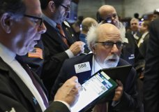 Peter Tuchman, right, works among fellow traders at a post on the floor of the New York Stock Exchange, Wednesday, March 4, 2020. Stocks are surging in early trading on Wall Street, led by health care stocks after Joe Biden scored a number of Super Tuesday wins. (AP Photo/Richard Drew)