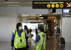 A pair of workers at Seattle-Tacoma International Airport wear masks Tuesday, March 3, 2020, in SeaTac, Wash. Six of the 18 Western Washington residents with the coronavirus have died as health officials rush to test more suspected cases and communities brace for spread of the disease. All confirmed cases of the virus in Washington are in Snohomish and King counties. (AP Photo/Elaine Thompson)