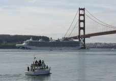 People watch from a boat as the Grand Princess cruise ship passes the Golden Gate Bridge in this view from Sausalito, Calif., Monday, March 9, 2020. The cruise ship carrying over a dozen people infected with the coronavirus passed under the bridge as federal and state officials in California prepared to receive thousands of people on the ship that has been idling off the coast of San Francisco. (AP Photo/Eric Risberg)